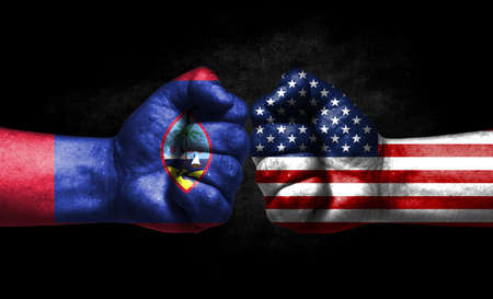The concept of the confrontation of peoples. The two fists are opposite each other. The hands are painted in the colors of the flags of the countries. America versus guam Banco de Imagens