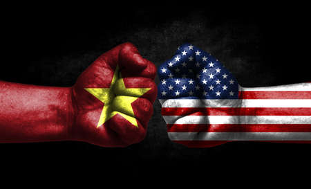 The concept of the confrontation of peoples. The two fists are opposite each other. The hands are painted in the colors of the flags of the countries. America versus Vietnam