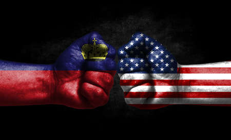 The concept of the confrontation of peoples. The two fists are opposite each other. The hands are painted in the colors of the flags of the countries. America versus liechtenstein Banco de Imagens
