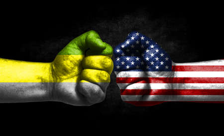 Two fists painted in the color of America and LGBT communities, a concept of confrontation. America vs Lithromantic pride