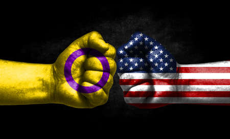 Two fists painted in the color of America and LGBT communities, a concept of confrontation. America vs Intersex pride