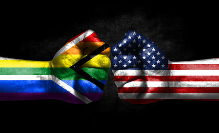 Two fists painted in the color of America and LGBT communities, a concept of confrontation. America vs Gay pride Flag of South Africa