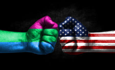 Two fists painted in the color of America and LGBT communities, a concept of confrontation. America vs Polysexuality Banco de Imagens