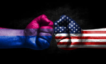 Two fists painted in the color of America and LGBT communities, a concept of confrontation. America vs Bisexual Banco de Imagens