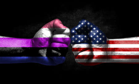 Two fists painted in the color of America and LGBT communities, a concept of confrontation. America vs Genderfluid