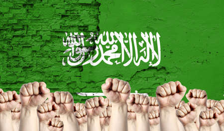 Raised fists of men against the background of the flag of Saudi Arabia painted on the wall, the concept of popular unity and the opinion of the majority. Reklamní fotografie