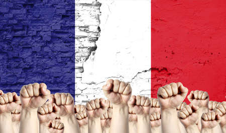 Raised fists of men against the background of the flag of France painted on the wall, the concept of popular unity and the opinion of the majority.