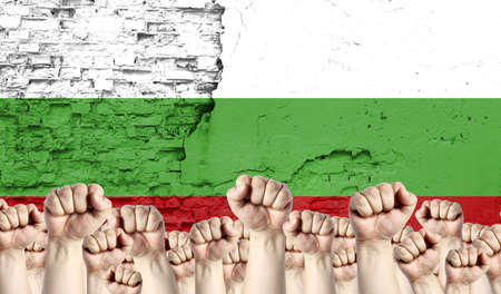 Raised fists of men against the background of the flag of Bulgaria painted on the wall, the concept of popular unity and the opinion of the majority.