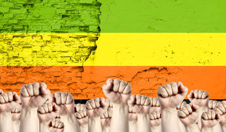 Raised fists of men against the background of the flag of Aromantic painted on the wall, the concept of popular unity and the opinion of the majority.