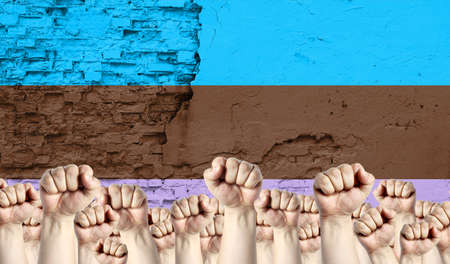 Raised fists of men against the background of the flag of Androsexual painted on the wall, the concept of popular unity and the opinion of the majority. Reklamní fotografie
