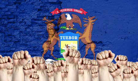 Raised fists of men against the background of the flag of State of Michigan painted on the wall, the concept of popular unity and the opinion of the majority. Reklamní fotografie