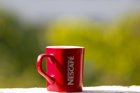 Red coffee cup on the window sill Editorial