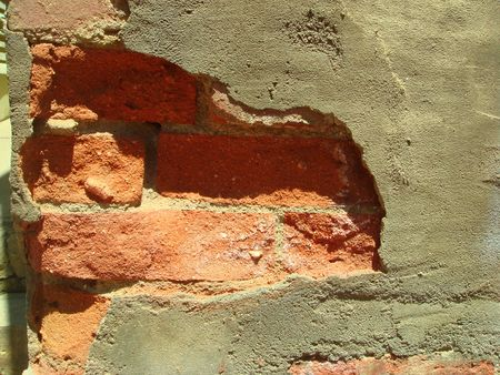 weakening: View of an old brick wall that is falling apart.               Stock Photo
