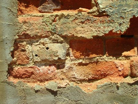 weakening: View of a wall made of bricks that is deteriorating.