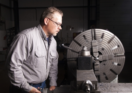 Worker using a metal lathe. photo