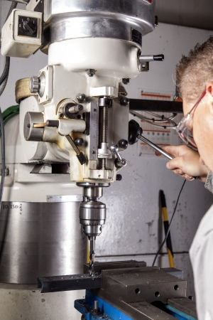 machine: Worker using a milling machine to drill a hole.