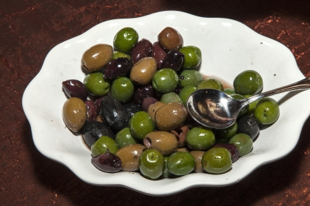 A plate of olives being served as an appetizer.