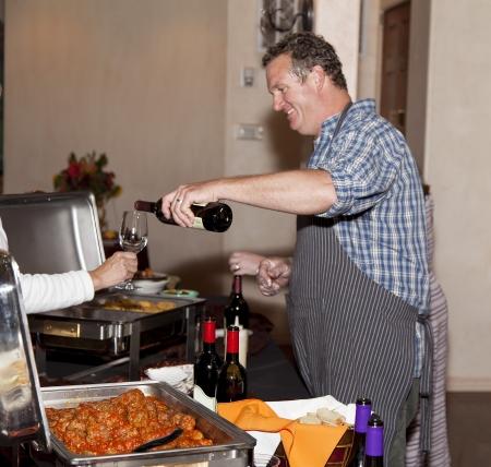 誰かのワイナリー イベントでワインのガラスを注ぐ人