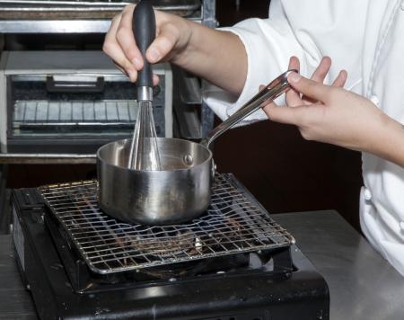 A chef heating a stirring a sauce