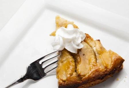 Slice of apple kuchen with whipped cream.