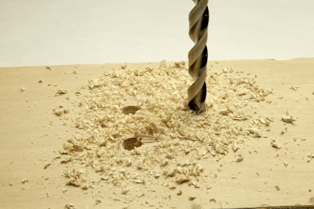 Close up of a drill bit making holes in a board