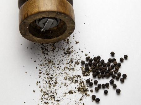 Part of a pepper grinder with ground pepper and peppercorns