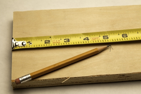 A tape measure being used to measure a board   版權商用圖片