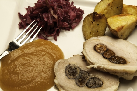 Roasted pork with figs and servings of potatoes, red cabbage and apple sauce