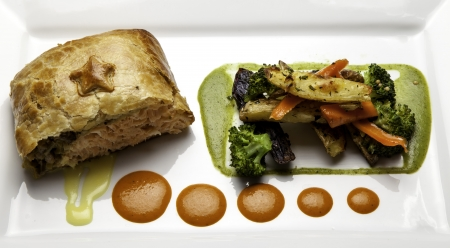 Zalm gebakken in bladerdeeg met geroosterde groenten. Stockfoto