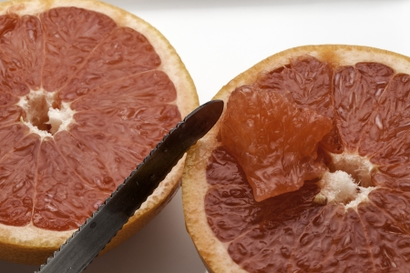 Red grapefruit sliced in half and prepared to be eaten  Фото со стока