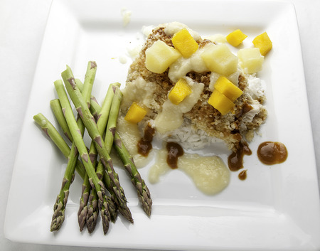 Fried fish fillet with fruit sauce and asparagus
