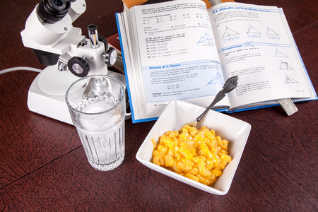 Student lunch of macaroni and cheese while studying. Фото со стока