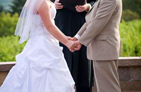 Bride and groom holding hands during wedding ceremonh