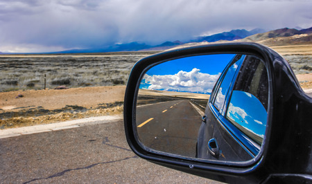 cloud capped: Rear view mirror with highway reflection on it Stock Photo