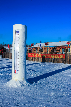 covered fields: Man-made thermometer in the winter field Editorial