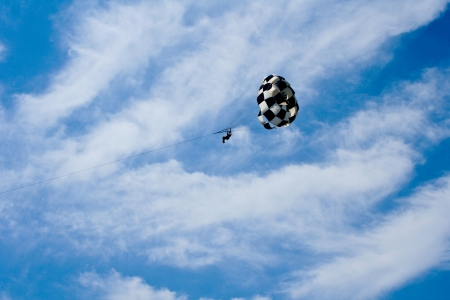 parachute jumping in the sky with clouds photo