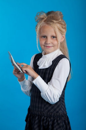 considers: Schoolgirl considers on the calculator on a blue background