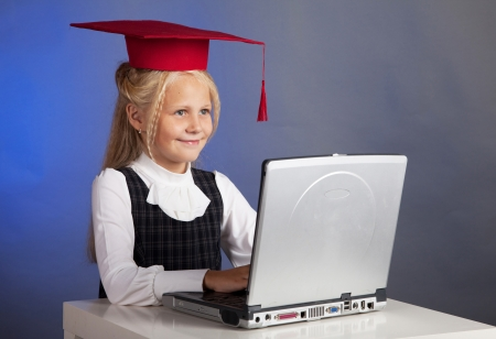 school girl in a red hat, working on a computer photo