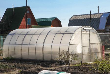 rural development: plastic greenhouses in the garden in spring