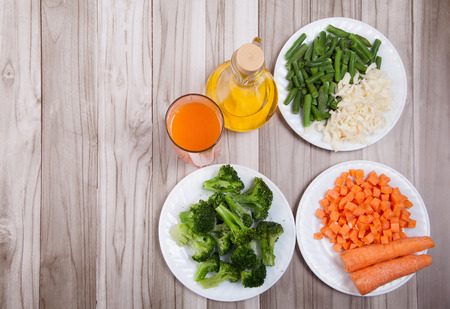 Carrots, broccoli, beans, cabbage, carrot juice and vegetable oil on a wooden table