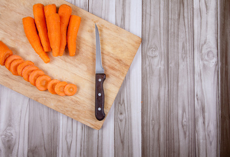 Carrots raw cut and knife on a wooden table Stock Photo