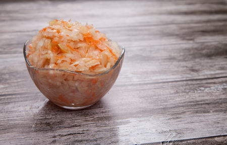 Sauerkraut in a glass cup on a wooden table