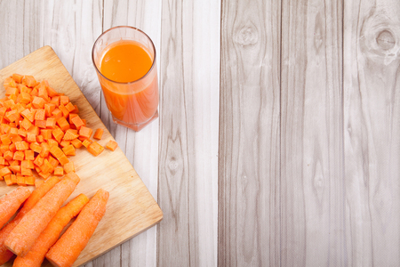 Carrots raw cut and carrot juice on a wooden table