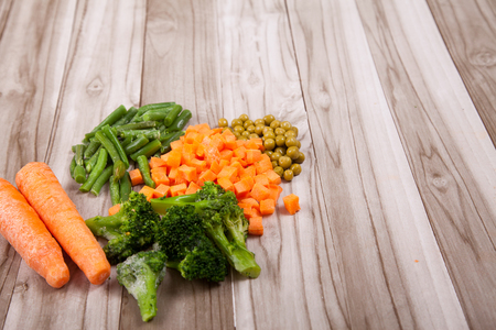 Carrots, broccoli, beans, green pea on a wooden table
