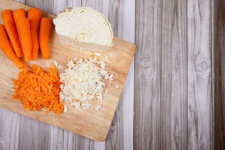 Cut raw carrots and cabbage and on a wooden table Stock Photo