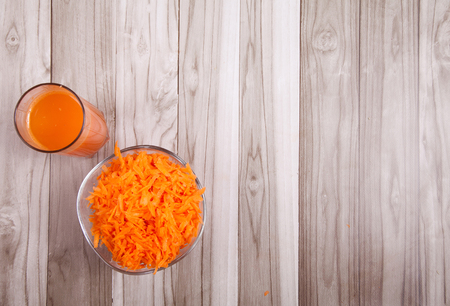 Carrots Grated raw and carrot juice on a wooden table