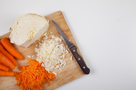 Cut raw carrots and cabbage and a knife on a white table