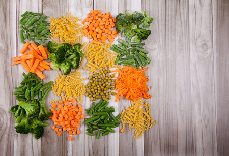 Carrots, broccoli, beans, green pea, paste on a wooden table Stock Photo