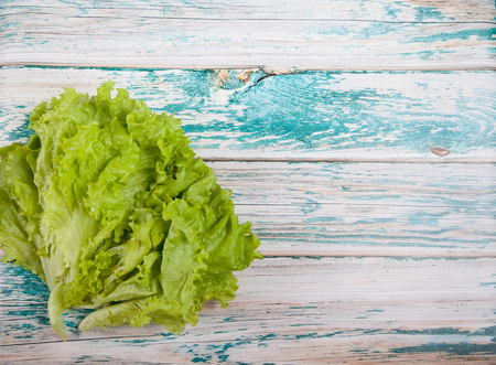 Green Lettuce leaves on a wooden background