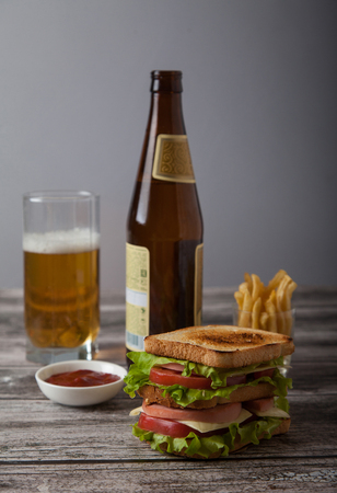 sandwich with beer, sauce, fried potatoes on a wooden table. Hor Standard-Bild